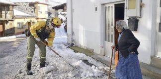 Un brigadista elimina el hielo ante la mirada de una vecina pertrechada con una azada. / BRIF TABUYO